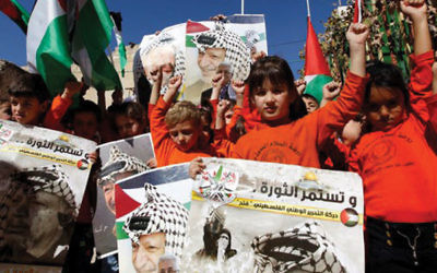 Palestinian children hold posters with the picture of former Palestinian leader Yasser Arafat and current Palesttinian Authority President Mahmoud Abbas during a rally in Hebron on Nov. 10, 2016, marking the 12th anniversary of Arafat's death.