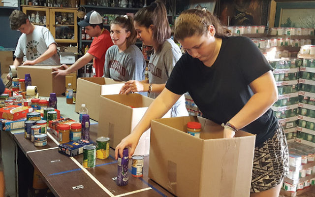 Teen volunteers pack boxes at the Jewish Family Service of Central New Jersey Kosher Food Pantry.