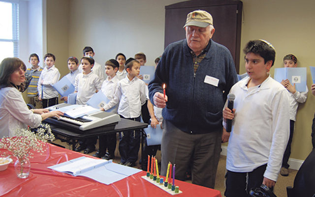 """Community nurse Karen Frank said finding ways to include elderly people in the celebrations """"might take a little more effort, but it's worth it."""" Here, children from the Jewish Educational Center have a Hanukka party with Cafe Europa mem"""