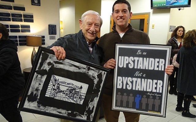 "Fred Heyman, left, holds a photograph of the infamous gates at Auschwitz while his ""twin,"" Howard Goldberg of Livingston, displays a poster with Heyman's motto: ""Be an upstander, not a bystander."""