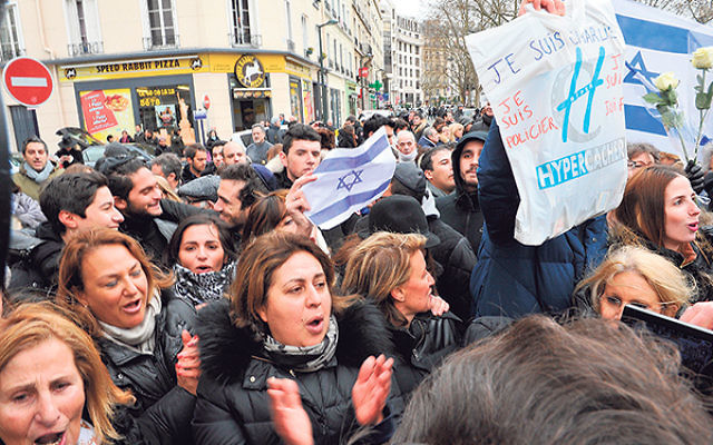 The crowd outside the kosher supermarket Hyper Cacher in Paris as Israeli Prime Minister Benjamin Netanyahu pays his respects to the victims of last week's terrorist attacks, Jan. 12.