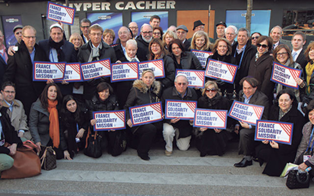 Jewish leaders on the solidarity mission to France sponsored by Jewish Federations of North America gather outside the Hyper Cacher kosher supermarket in Paris where four Jews died at the hands of Muslim extremists.