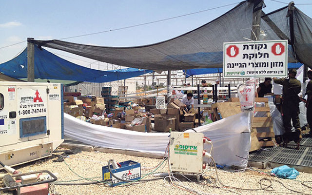 With the aid of philanthropic funds, soldiers are fed in a tent at Moshav Maslul in Merchavim.