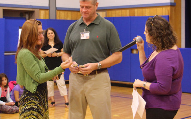 Michael Mault receives a Tefilat Haderech prayer keychain from GOA lower school principal Carrie Siegel, right, and program director Gena Jarmel.