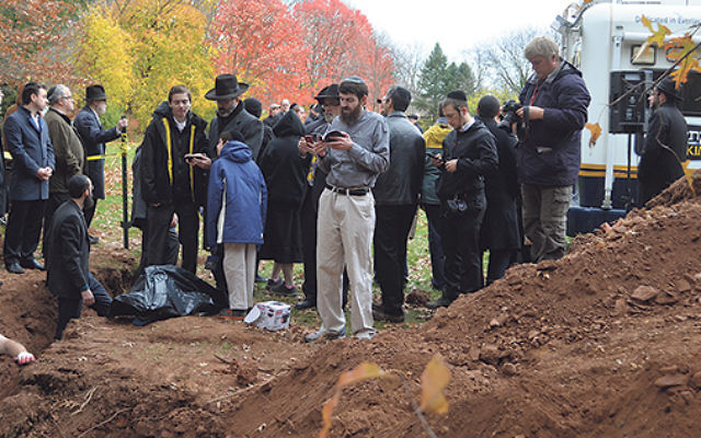 Prayers are recited as the holy items are buried at the Poile Zedek Cemetery.