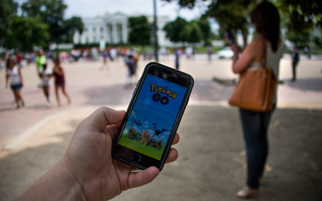 A man holds up his cell phone with a screen shot of the Pokemon Go game as a woman searches on her cell phone for a Pokemon in front of the White House in Washington, DC, July 12, 2016.