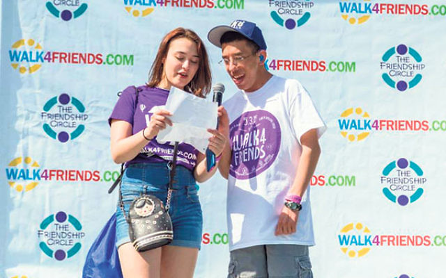Friendship Circle volunteer Eva Poleschuk introduces fellow volunteer Sam Goto, a former FC client, to the crowd at the 2015 Walk4Friends.