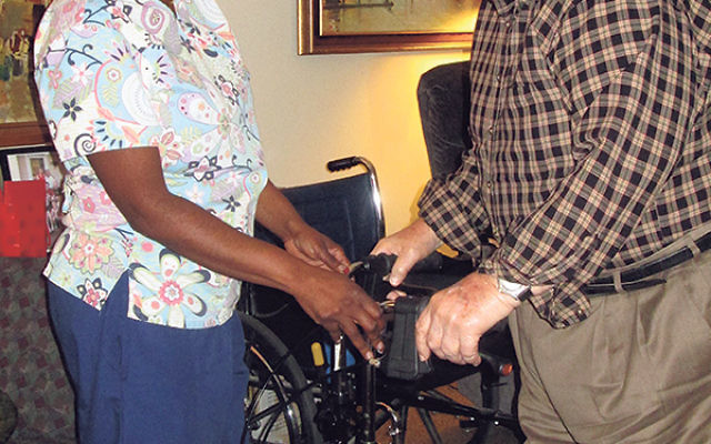 Victor Walcoff, who resides at Abrams Assisted Living Residence at Greenwood House, is assisted by Gwen Hilton, a certified home health aide at the facility.