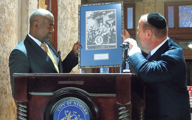 At the menora-lighting ceremony, Miles Berger presents Mayor Ras Baraka with a photograph of President John F. Kennedy speaking on the steps of Newark City Hall on Oct. 12, 1962.
