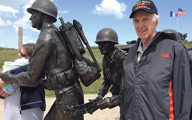 Peter Hirschmann alongside the statue on Utah Beach that jogged his memories of the weapon he carried during the war.