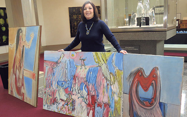 Three of the nine paintings by survivor Yonia Fain are shown by Barbara Wind, director of the Holocaust Council of Greater MetroWest.