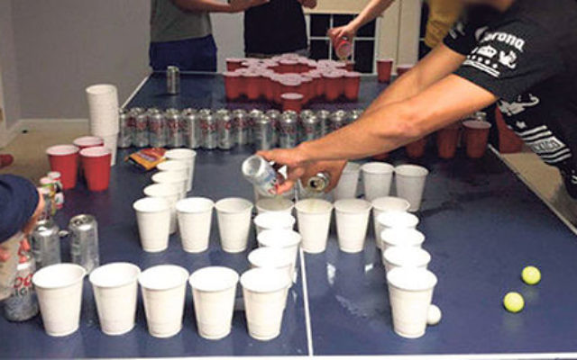 "A student pours beer into a cup before a game of ""Holocaust Pong."""