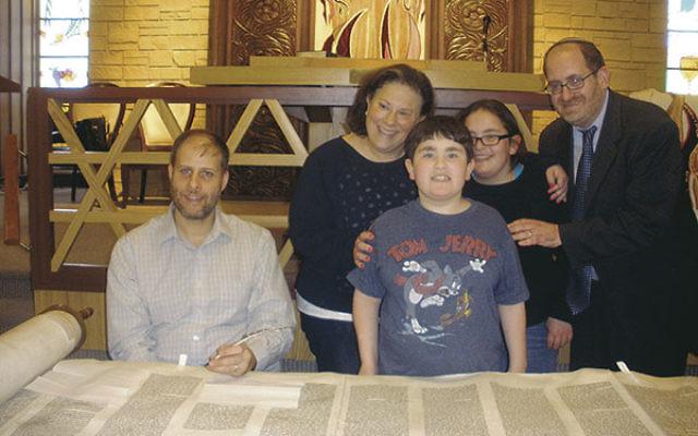 Rabbi Eli Garfinkel and his wife, Naomi Lasky, and their nine-year-old twins, Sari and Josh, with scribe Rabbi Daniel Wizodsky.