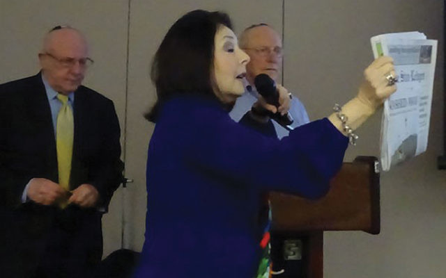 """Barbara Wind, director of the Holocaust Council of Greater MetroWest NJ, holds up a copy of The Star-Ledger from Jan. 25, 2017, documenting the appearance of twins Bernard and Henry Schanzer, survivors of the Holocaust at a """"lunch and learn"""" l"""