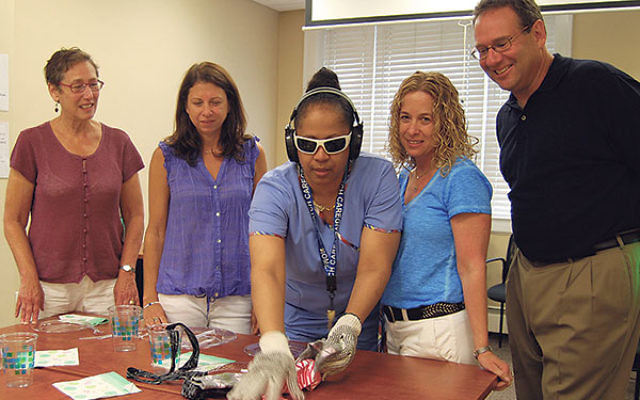 """Certified home health aide Shirley Baldwin, center, outfitted with the """"virtual dementia"""" gear, tries out some tasks, watched by Homewatch staff, from left, Karen Frank, Margo Weill, Melissa Bressler, and Larry Aronson."""