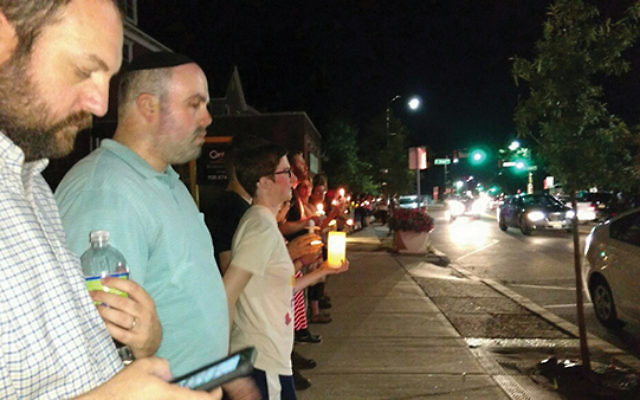 Rabbi Bryan Kinzbrunner, far left, joins Councilman Josh Fine and hundreds of others lining up along Raritan Avenue in downtown Highland Park. Photos by Debra Rubin