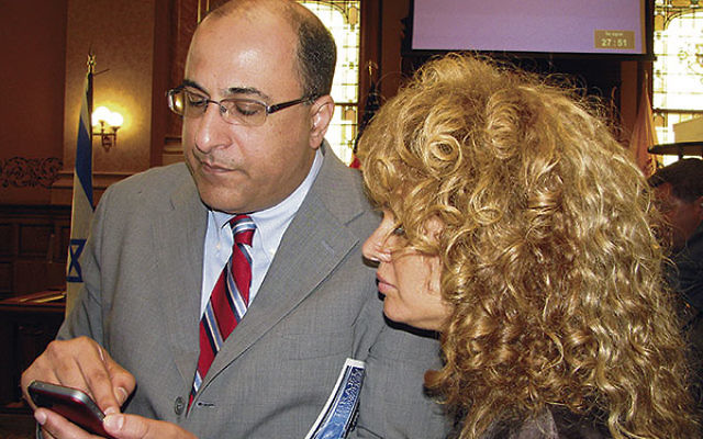 Israeli Consul General Ido Aharoni shows his cellphone apps to Israeli-born violinist Miri Ben-Ari.
