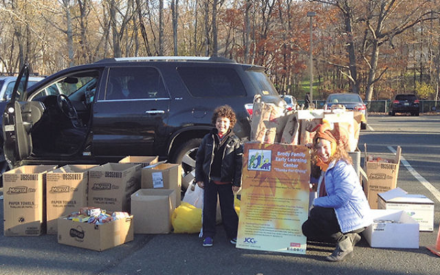 JCC early childhood learning coordinator Randi Sosny-Handler works with children to get the Thanks-for-Giving food donations ready for delivery.
