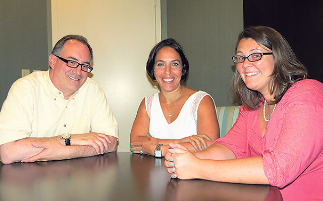 Reuben Rotman, executive director of the Jewish Family Service of MetroWest NJ, discusses his agency's expansion of mental health services for teenagers with two JFS social workers, Robyn Krugman, center, and Sara Mendez Emma.