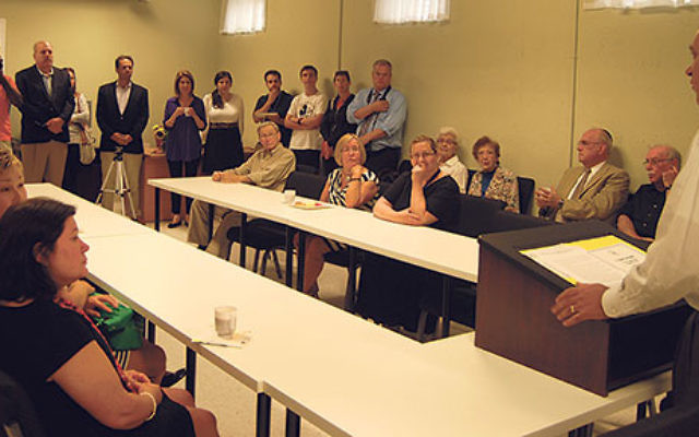 JFS of Central NJ president David Levenberg, right, addresses benefactors, staff, and supporters gathered for the opening of the agency's new home health aide training center; to his left is Brunilda Moriarty, representing the foundations that provi