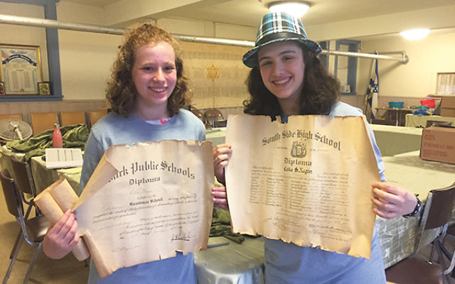 Shayna Mandelbaum, at right, and another Mitzvah Mania volunteer hold documents uncovered at Ahavas Sholom in Newark.