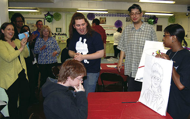Staff and friends applaud as a JVS of MetroWest client shows off the picture she drew of her friend and fellow client at the Autism Awareness Month party.