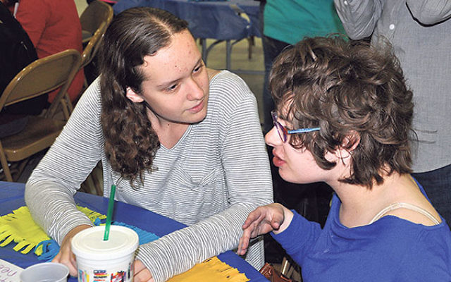 Sarah Cehelyk, left, and her friend work together on a blanket for Ronald McDonald House.