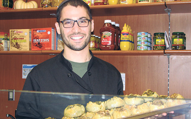 Kalman Goodman serves up a tray of knishes at his glatt kosher restaurant that opened in September in Springfield.