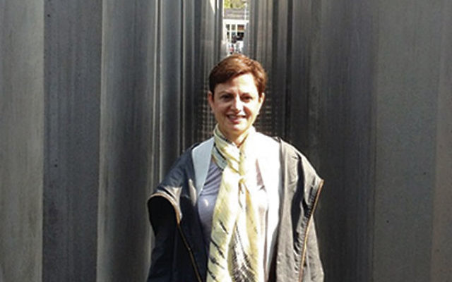 Genesia Kamen stands amid the concrete blocks at the Memorial to the Murdered Jews of Europe in Berlin.