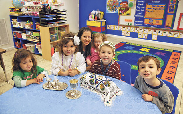 Students join teacher Lori Hirsh in celebrating an early Shabbat at the Yeshiva at the Jersey Shore preschool, then housed at Young Israel of East Brunswick. The Orthodox yeshiva is forming a partnership and moving to the Conservative East Brunswick Jewis