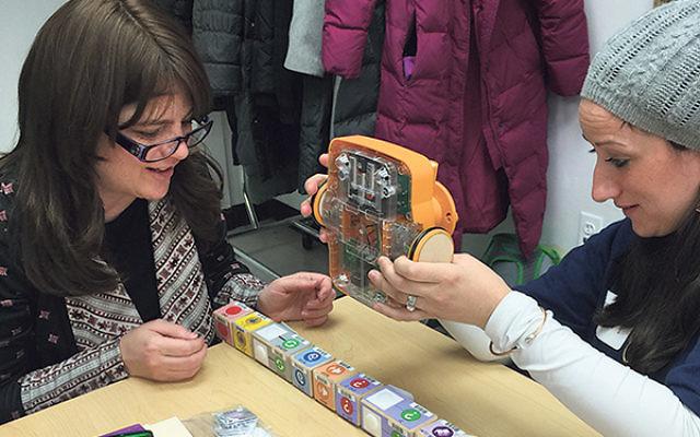 Lisa Bond, left, JEC's Yeshiva of Elizabeth early childhood director, and educator Sarah Cohn build a Kibo robot.