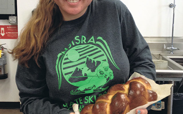 Knead to Feed volunteer Raigne Adler holds a hallah she made at a recent baking session at Har Shalom.
