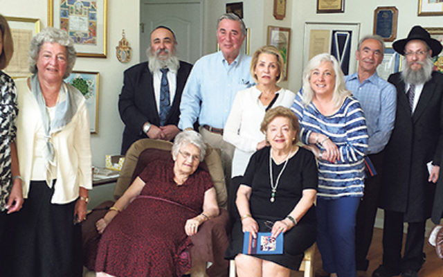 Clara Kramer, in the armchair, hosted a gathering to talk about raising aid for Chesed Shlomo in Zhitomir, Ukraine, named for her late husband, Sol. With her are, from left, Elyse Deutsch, Freida Posnock, Rabbi Mordechai Kanelsky, Leonard Posnock, Toby Go