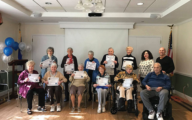 """ARTS By The People executive director Paul Rabinowitz, back row, right, with some of the writers from Lester Senior Housing who contributed to """"Revolving Doors"""" at the project's debut. Photo by Keisha McDonald"""