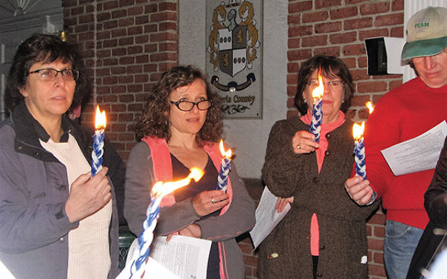 About 35 people attended a Havdalah service on the steps of Rodney Frelinghuysen's Morristown office on April 15. From left, Sherri Heller of Sparta, unidentified, Amy and Michael Ipp of Livingston. Photos by Johanna Ginsberg