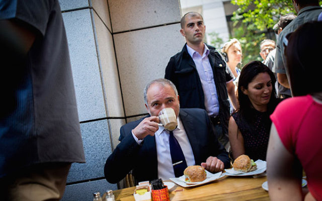 Israeli Defense Minister Avigdor Liberman drinking coffee at the Sarona Market in Tel Aviv, a day after a deadly attack at the pedestrian mall, June 9, 2016. (Miriam Alster/Flash90)