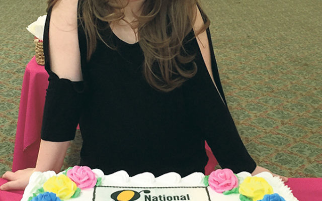 Lindsay Zuckerman displays the cake she shared at the Jan. 31 dance-athon benefit at Pine Brook Jewish Center.