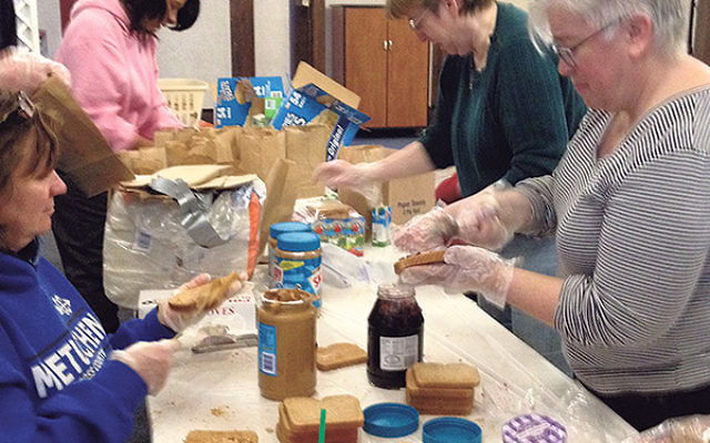 Volunteers at Temple Emanu-El assemble peanut butter and jelly sandwiches for the homeless.