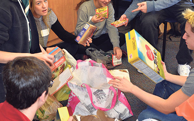 On Mitzva Day, the Sandy Senior Fellows helped organize a food drive; from left, Sawyer Malkin, Paul Gurman, Emily Esquenazi, Jen Koppel, and Matt Fryfield.