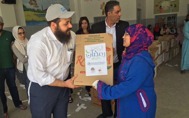 Chabad Rabbi Levi Banon handing a Ramadan gift bag to a Moroccan Muslim woman. (International Fellowship of Christians and Jews)