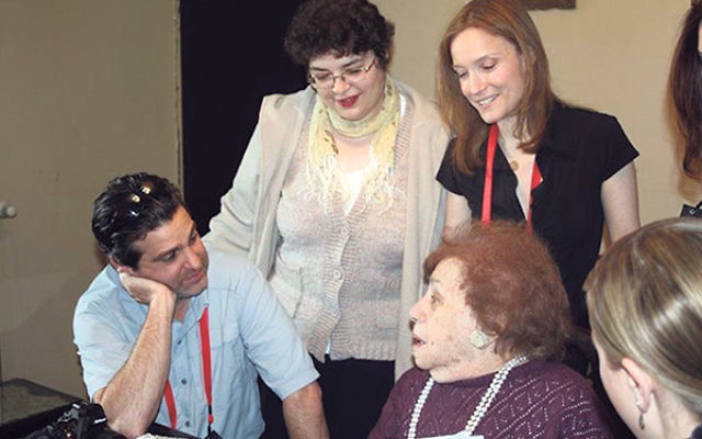 Lee Murnick, right, stands behind Bella Holban, 93, a Holocaust survivor living in Bucharest.