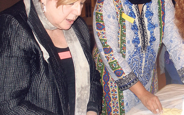 Rabbi Shira Stern, left, teaches Fatima Masood how to braid a loaf of hallah.