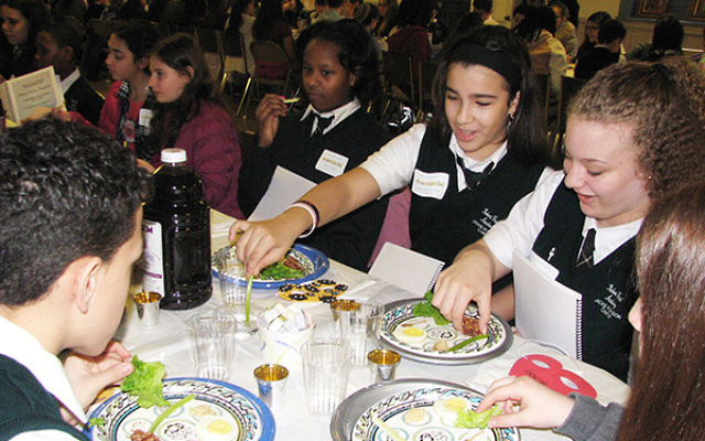 Jewish and non-Jewish students from four area schools dip karpas at a model seder at Congregation Ahavas Sholom in Newark. Photos by Johanna Ginsberg