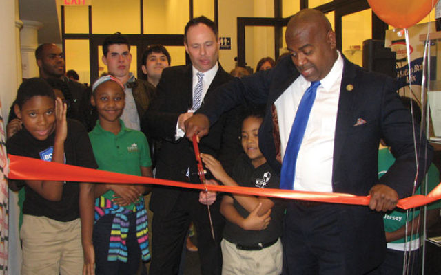 Mayor Ras Baraka, right, cuts the ceremonial ribbon with Manischewitz CEO David Sugarman, surrounded by children from the Boys and Girls Club of Newark and students from Rae Kushner Yeshiva High School.