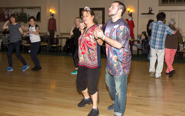 Israeli folk dance instructor Elyse Litt tries out steps with her son, Jake Altholz, who choreographed the dance in memory of his father. Photo by Moshe Gordon