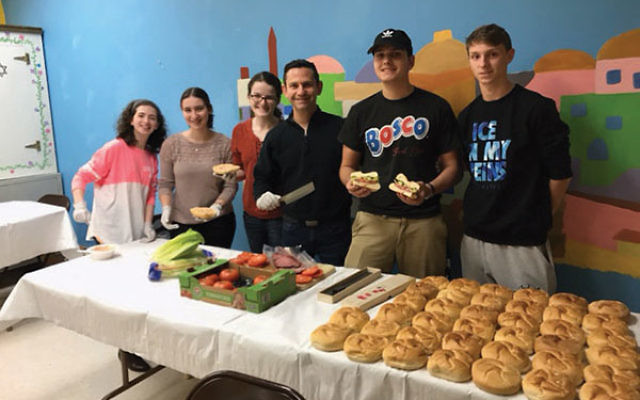 USY teens and Cantor Menachem Toren, third from right, make sandwiches for dinner guests to bring home. From left, Liora Finkel, Sara Schneiderman, Carly Goldsmith, Yuval Toren, and Max Weinstein.