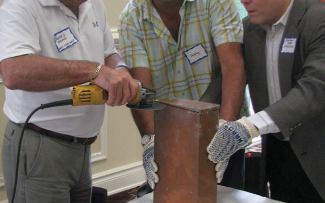The time capsule is carefully opened at Pine Brook Jewish Center.