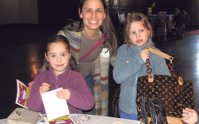 Rachel Zorel of South Orange with daughters Shaya, eight, center, and Ami, six, packing purses to help women in need.