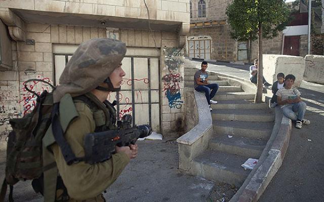 Palestinians watch an Israeli soldier on patrol on a street in Hebron.