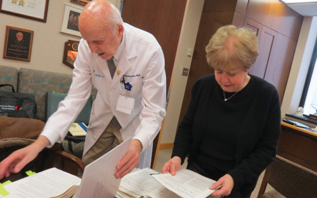 Victor Parsonnet and Linda Forgosh, executive director of the Jewish Historical Society of NJ, examine some of the Newark Beth Israel Hospital documents he donated to the JHS archives in March 2015.